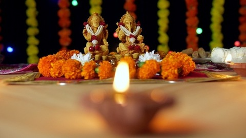 Bokeh shot - Burning Diya with Indian gods Ganesh Ji and Laxmi Ji - Indian festival Diwali