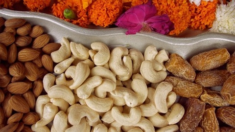 Pan shot of a silver dry fruits tray kept on a floral platform for Diwali celebration
