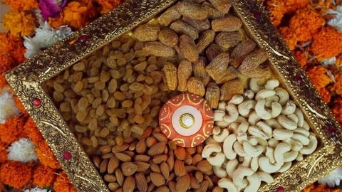 Top view shot of a rotating golden tray with various dry fruits on the occasion of Diwali