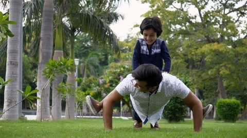 Handsome man doing push-ups with the boy on his back in casual wear - leisure time