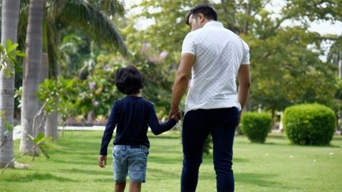 Back view of happy father and son walking while holding hands in a summer park - father's day