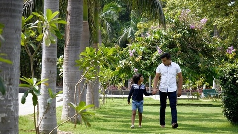 Pan shot of a boy holding his dad's hand while walking around in the garden - happy family