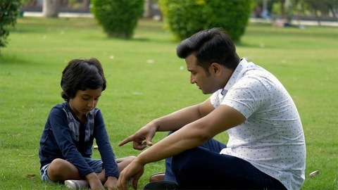 Angry Indian father scolding his young son for plucking grass - save the environment