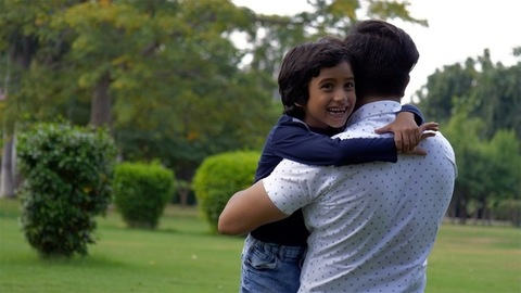 Indian father and son happily enjoying a Sunday weekend together in a park