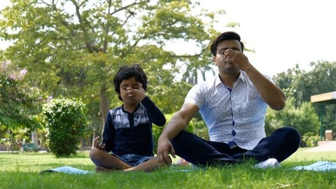 Indian father and little son doing Anuloma Viloma Pranayama together - healthy breathing