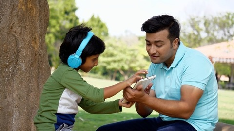 Indian father and son using a tablet with blue headphones while spending time together