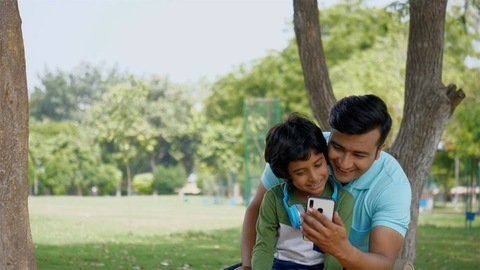 Young father and his son waving a 'Hi' while having a conversation on a video call - technology concept