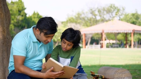 Loving parent reading an interesting book to his little son - love and family concept