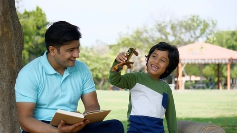 Young father and son happily spending a Sunday weekend together in a park - leisure time