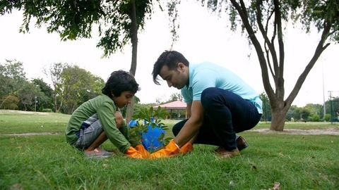 A young attractive man gardening a little sapling with his son in a park - ecology concept
