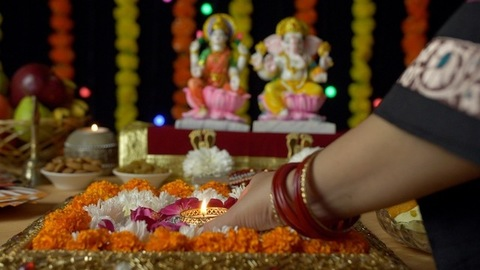 Indian female decorating flower rangoli with burning Diya on Dipavali - the festival of India