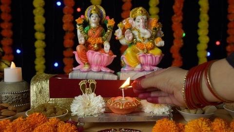 Shot of an Indian female's hand lighting up a Diya in front of Ganesh Ji and Laxmi Ji on Diwali