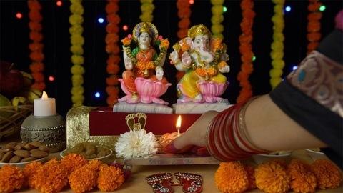 Hands of a female putting a burning Diya in front of Ganesh Ji and Laxmi Ji on Diwali festival