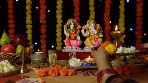 Indian female praying in front of Ganesh Ji and Laxmi Ji with a Puja thali on Diwali