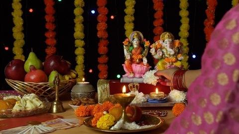 Over the shoulder shot of an Indian female praying in front of Ganesh Ji and Laxmi Ji - Diwali Puja