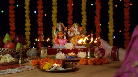 Over the shoulder shot of a female worshipping Lord Ganesha and Goddess Laxmi - Diwali puja