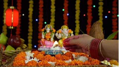 Shot of an Indian female's hand lighting up a Diya in front of Ganesh Ji and Laxmi Ji - Diwali festival