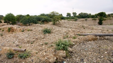 Long shot of an endless dumping ground full of household wastes in India