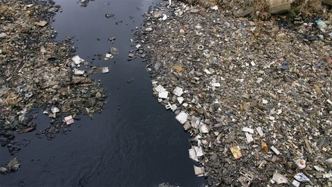 Top view of a polluted drainage ditch full of dirty water and rubbish garbage