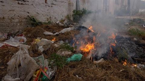 A burning garbage dump polluting the environment by producing harmful smoke - global warming