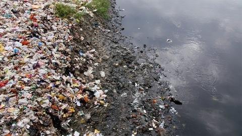 Tilt shot of garbage like plastic bags, bottles, household waste, etc at the side of a river