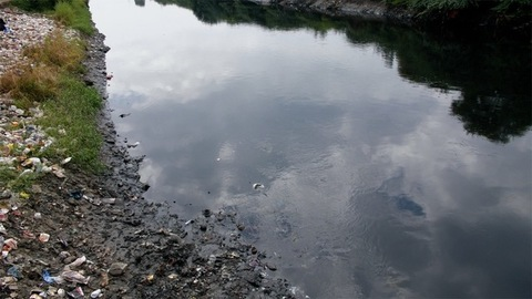 Dirty and polluted riverside with plastic bottles, bags and other garbage