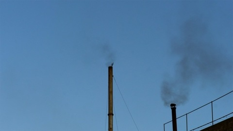 Harmful smoke coming out from an industrial chimney pipe causing air pollution