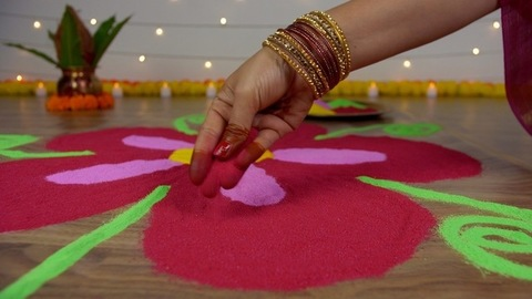 Hands of a traditional Indian woman making colorful rangoli for Diwali - the festival of India