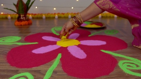 Indian female's hands drawing rangoli on the floor for the festival of Diwali/Dipavali