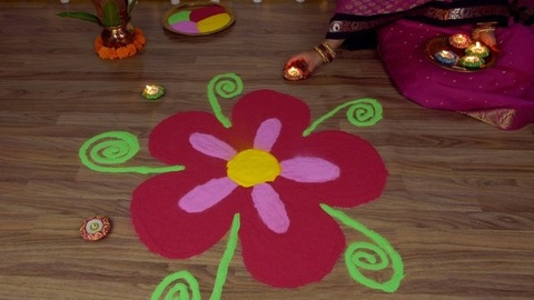 Hands of a traditional woman decorating rangoli with oil lamps on the occasion of Diwali