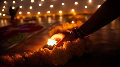 Bokeh shot of Indian female's hands decorating burning Diyas - Diwali decoration