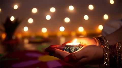 Beautiful hands of a female with mehndi, bangles and a glowing oil lamp - Diwali/Dipavali