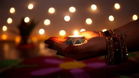 Bokeh shot - Hands of a traditional woman holding a burning Diya on the festival of Diwali
