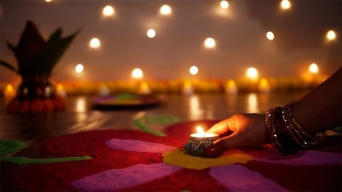 Hands of a traditional woman placing a burning Diya in the center of a beautiful rangoli - Diwali festival