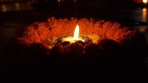 Pan shot of a colorful burning Diya kept on a floral platform on the festival of Diwali