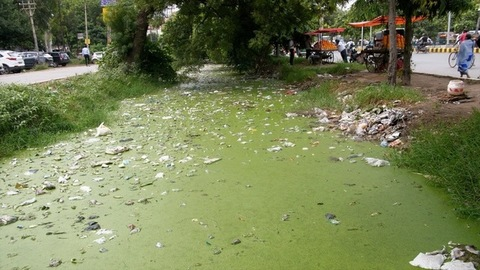 Rubbish household waste scattered in a roadside water drainage - bad ecology